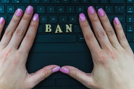 womens hand on the laptop keyboard with the letters BAN Stock Photo