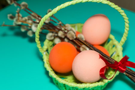 in the basket painted eggs on a turquoise background. happy Easter concept