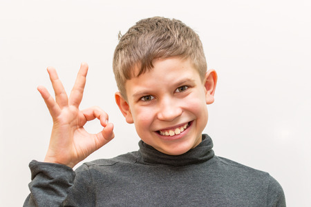 teen boy shows OK gesture on white isolated background