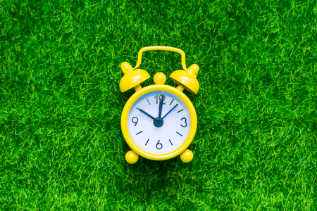yellow alarm clock on the grass. Concept of time