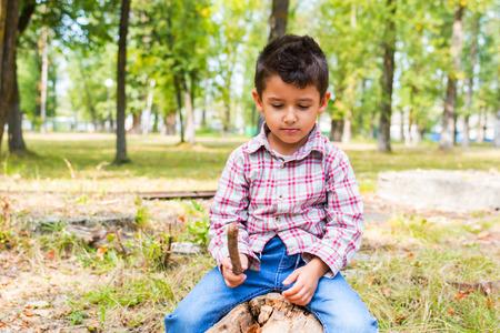 niño matón con un palo en el parque en otoño