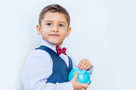 pensive boy with piggy Bank in his hands on white background