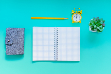 Desktop with notebook, alarm clock, pencil. Blank for mock up