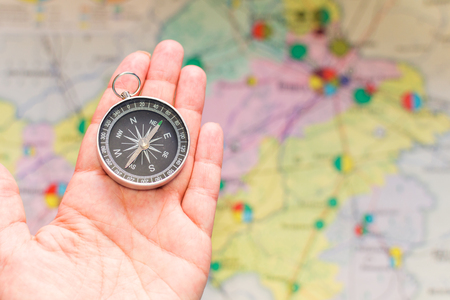 compass in hand on a background map
