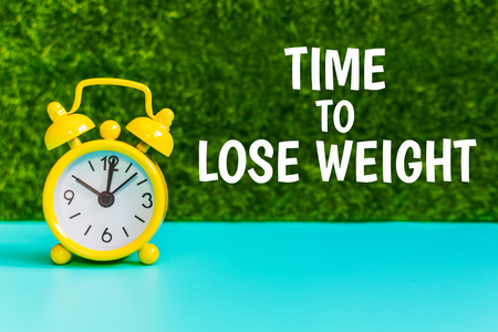 yellow alarm clock on the grass background with the inscription Time for weight loss