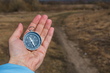 compass in a female hand on a background of nature