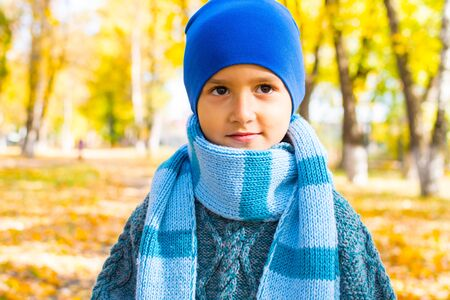 portrait of a brown-eyed boy in a hat and a large knitted scarf in autumn