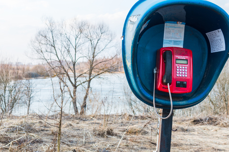 April 2019, Russia, village Snopot. Single telephone booth in the countryside near the river