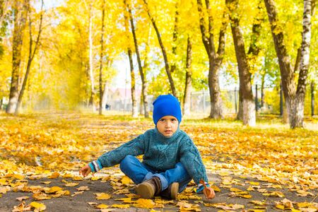 boy in sweater and hat sitting in autumn Park on the ground