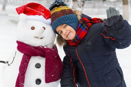 chłopiec 5 lat stojący w pobliżu bałwana na zewnątrz w zimie i uśmiecha się. Zdjęcie Seryjne