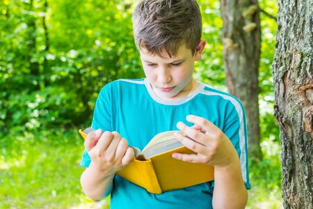teen boy stands with a book near a tree in summer