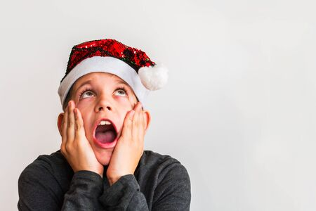 surprised boy in Santa hat on white background