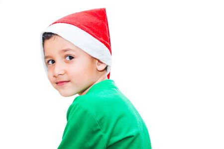 boy in Santa hat sideways on white isolated background 版權商用圖片