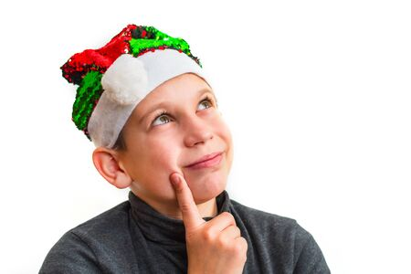 pensive boy in Santa hat on white isolated background
