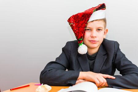 teenage boy in Santa's hat at the table with books Stock Photo