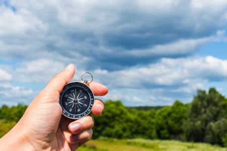 compass in hand close-up on the background of the summer landscape Stock Photo
