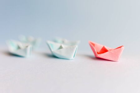 several blue and one red paper boat. The concept of leader, success. Stockfoto
