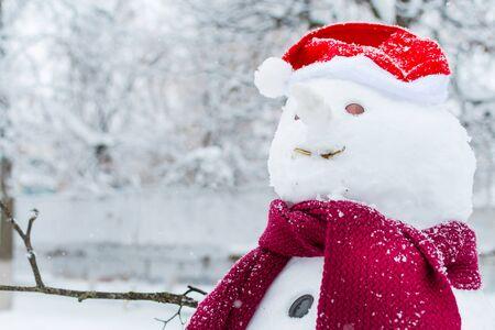 pupazzo di neve con cappello e sciarpa in primo piano all'aperto