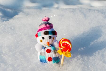 small knitted snowman with candy in the snow