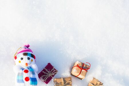funny toy snowman with gifts in a snowdrift with a copy of space