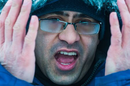 disgruntled man with misted glasses. the problem of wearing glasses in winter Stockfoto