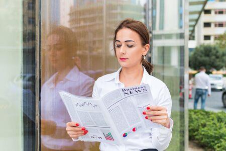 femme d'affaires lisant un journal à l'extérieur de la ville Banque d'images