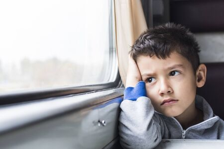 boy 5 years goes to in a train and with sadness looks in window