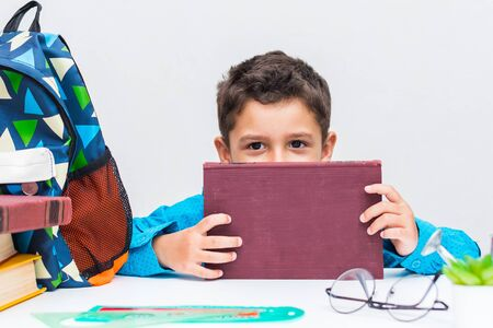 A dark-haired little boy in a blue shirt at a table with books.  The boy hides behind a book.