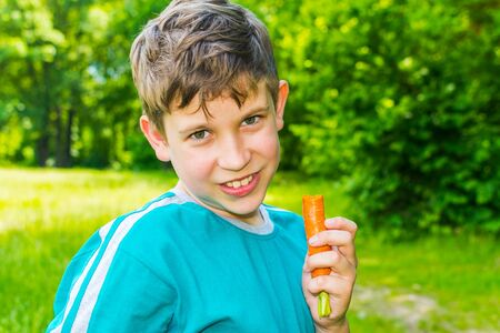 teen boy with a carrot in a forest