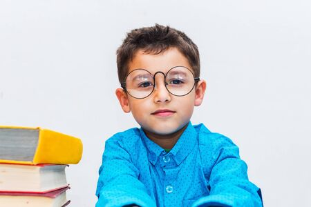 cute boy in glasses sitting at a Desk with books