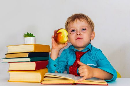 preschool boy at the Desk eating an apple. snack during classes. Archivio Fotografico