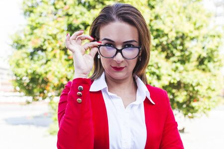 portrait of a business woman with glasses in the open air.  A woman in a red suit is holding glasses. Archivio Fotografico
