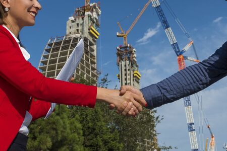 business partners shake hands. A woman and a man at a business meeting in the open air on the background of a house under construction.