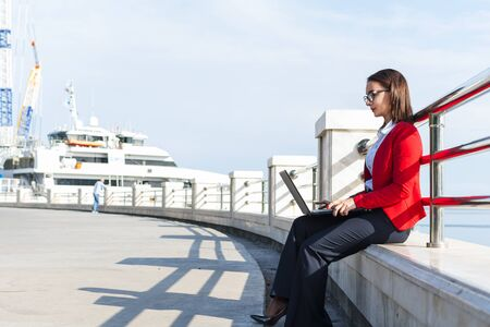 Business woman working with a laptop outdoors. A woman with a laptop.