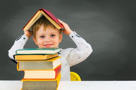 preschooler boy sits at a Desk on the background of the blackboard,  and holds a book on his head.