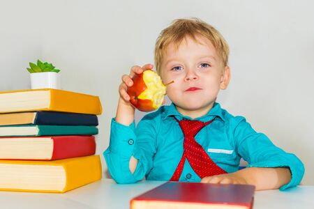 preschool boy at the Desk eating an apple. snack during classes. Stok Fotoğraf