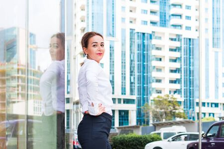 business positive woman on the background of buildings in the city center