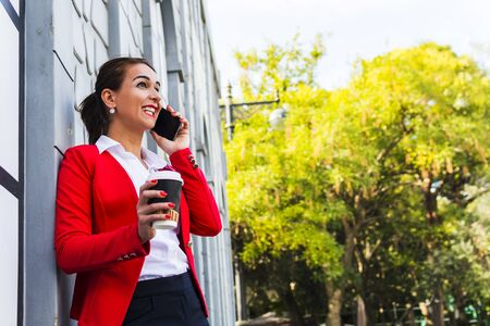business woman having fun talking on the phone outdoors. business lady with coffee emotionally talking on the phone.