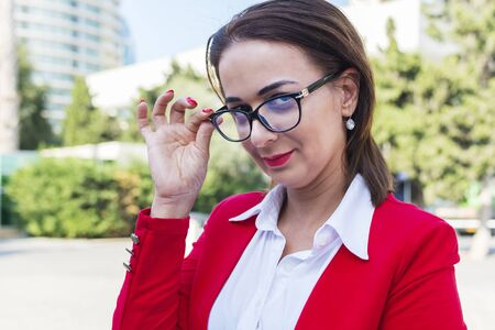 portrait of a business woman with glasses in the open air.  A woman in a red suit is holding glasses. Stok Fotoğraf