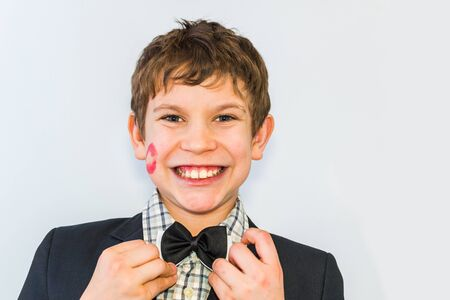 portrait of a teenage boy with a lipstick print on his cheek