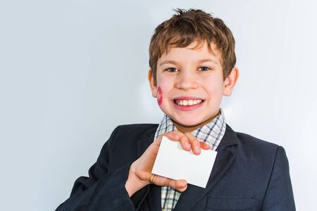 teen boy with lipstick print on cheek holding empty card