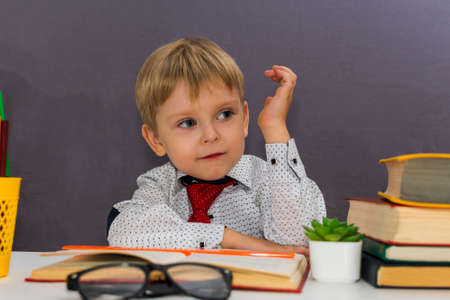 boy stretches out his hand. a preschooler sits at a Desk