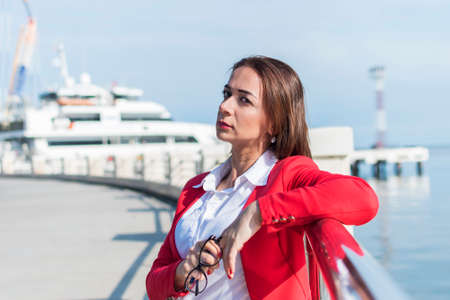 business woman in a red suit stands by the sea