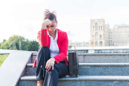 sad woman in a business suit sits on the steps. a business woman has problems.