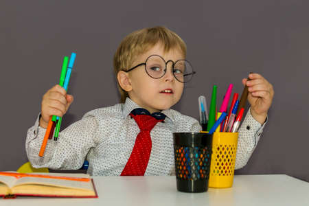 pre-school boy with markers in his hands. A blond boy is sitting at a Desk.