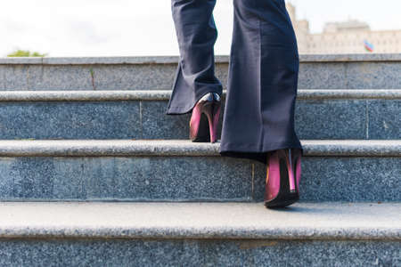 business woman climbs the stairs. Feet on the steps