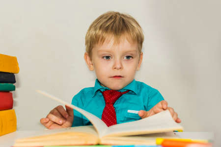 serious preschool boy reads a book