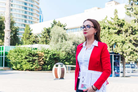 business woman in a red jacket on a city street.
