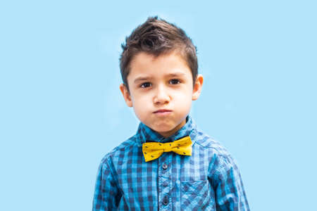 portrait of a boy with puffed cheeks on a blue background Stock Photo