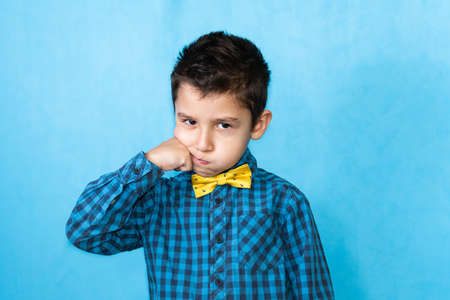 portrait of a little boy on a blue background. Boy showing fight gesture